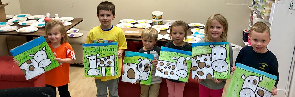 Happy kids with their cow artwork